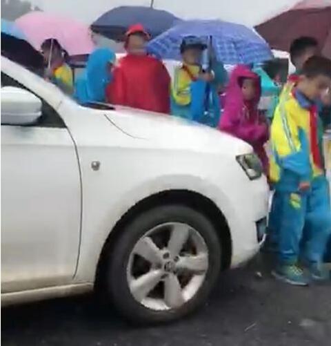 下雨天轿车顶着学生往前开 车主主动致歉